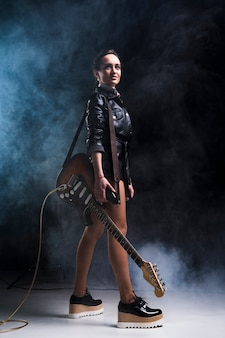 Rock star woman with electric guitar on stage