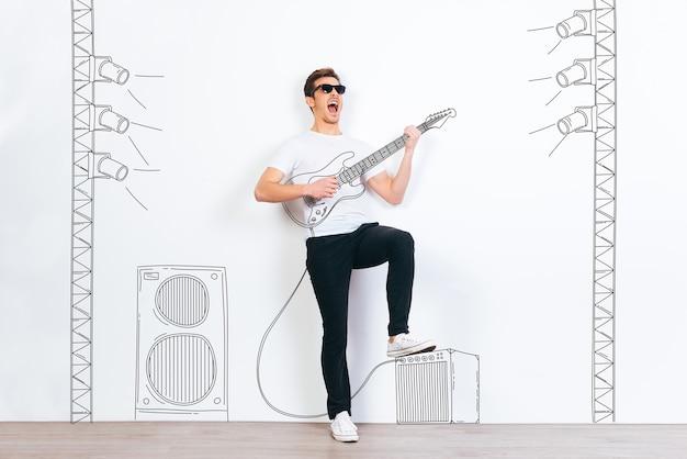 Рок-звезда! молодой красавец в солнечных очках играет на гитаре и держит рот открытым, стоя на белом фоне с иллюстрацией стереоколонны и сценического света