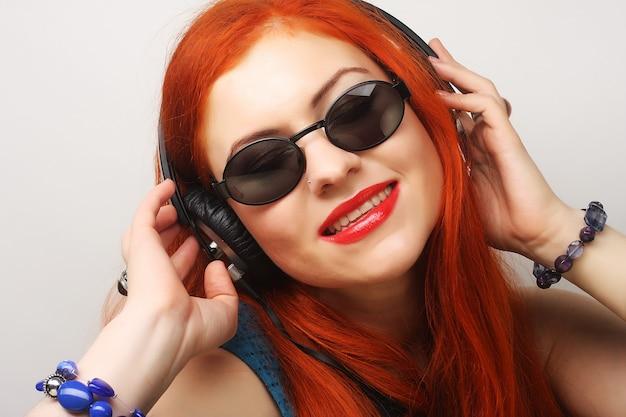 音楽を聴いているヘッドフォンでロックスタイルの女性