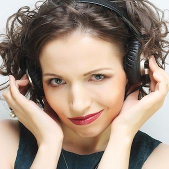 Женщина в стиле рок с наушниками, слушающая музыку