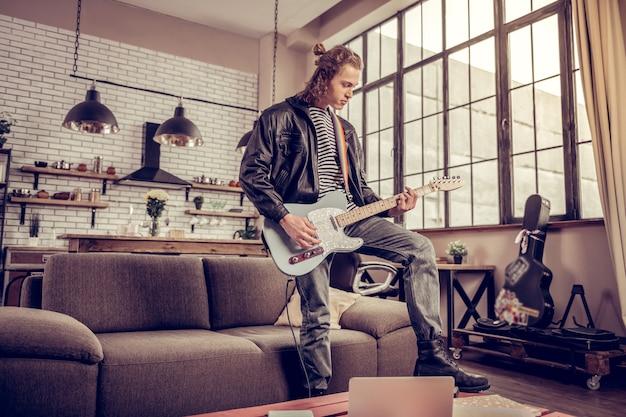 ロックタイム。居間でリハーサルをしている現代の有名なロックバンドの参加者