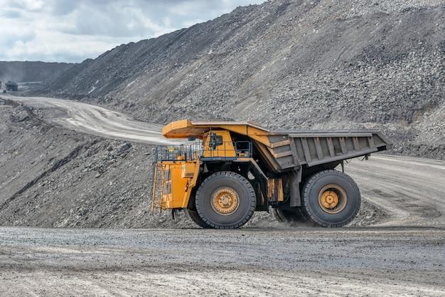 Перевозка горных пород самосвалами. большой карьерный желтый грузовик. транспортная индустрия.