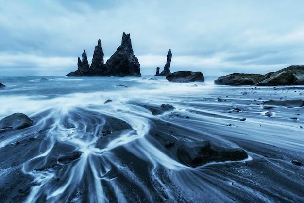 Рок тролль пальцы ног. рейнисдрангарские скалы. черный песчаный пляж