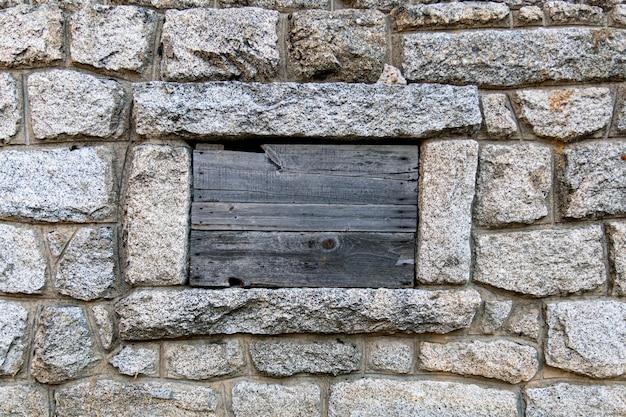 岩壁と木製パレットで覆われた閉じた窓板張りの窓