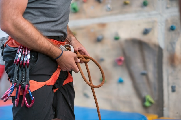 Rock wall climber wearing safety harness and climbing equipment indoor, close-up image