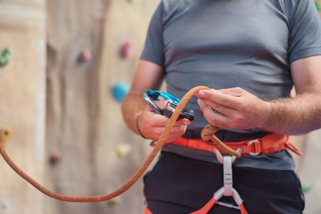 Rock wall climber wearing safety harness and climbing equipment indoor