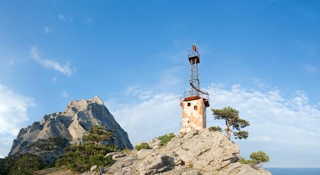 青空の背景の斜面に針葉樹と古い灯台のある岩(「sokol」岩、「novyj svit」保護区、クリミア半島、ウクライナ)。 5ショットステッチ画像。