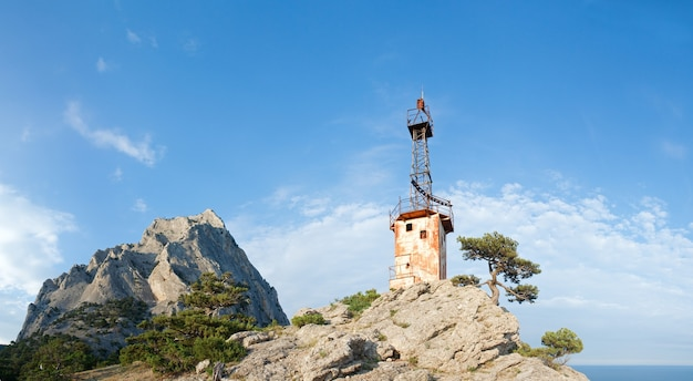 Rock with conifer trees and old lighthouse on slope on blue sky background (