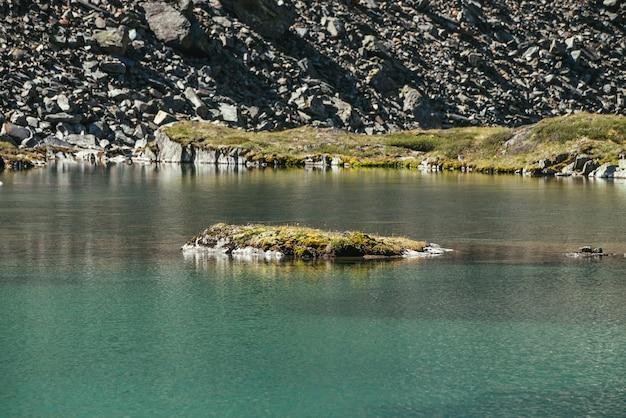 ターコイズブルーの山の湖でコケや草で岩。紺碧の氷河湖と澄んだ水の中の苔むした岩のある風光明媚な日当たりの良い風景。山の湖の水面と美しいカラフルな風景。