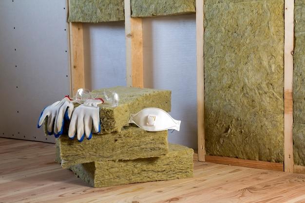 コールドバリア用のロックウールとグラスファイバーの断熱材。グラスウールで作業するためのツール:保護メガネ、メガネ、マスク。暖かい家、経済、建設、改修のコンセプト。