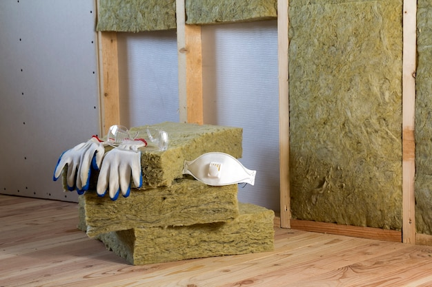 Rock wool and fiberglass insulation staff material for cold barrier. tools for work with glass wool: protective goggles, glasses and mask. warm home, economy, construction and renovation concept.