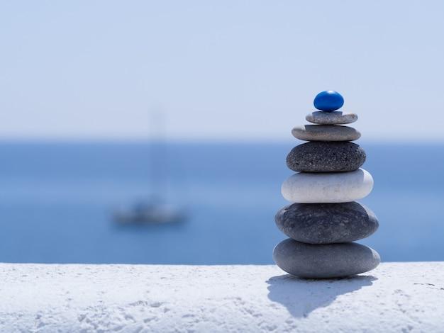 Рок-дзен-пирамида из разноцветной гальки на фоне моря и лодки. концепция жизненного баланса, гармонии и медитации