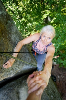 Rockclimber help to female climber to reach top of mountain