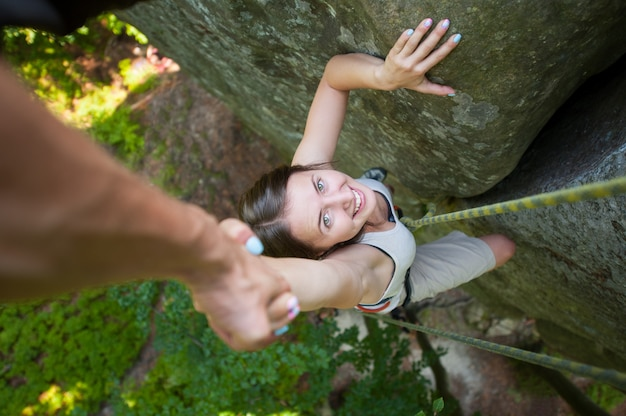 Rockclimber helping to female climber to reach top of mountain