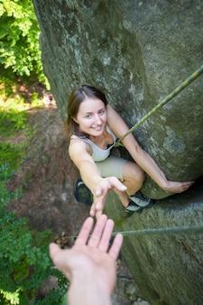 Rockclimber помогает женскому альпинисту достичь вершины горы