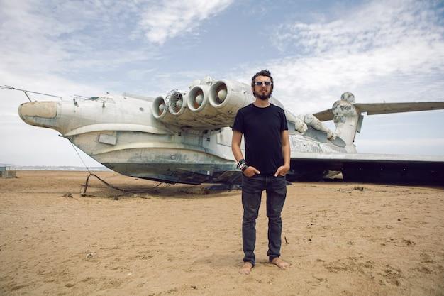 ダゲスタンの夏のビーチで放棄された飛行機の背景に立っている黒い服を着た子供ロッカーの男の子