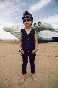 黒い服を着た子供ロッカーボーイは、ビーチで放棄された飛行機の背景に立っています