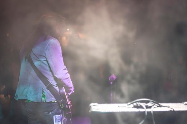 Рокер сзади призывает толпу со сцены, фильтруемую искусственным дымом и световыми эффектами.