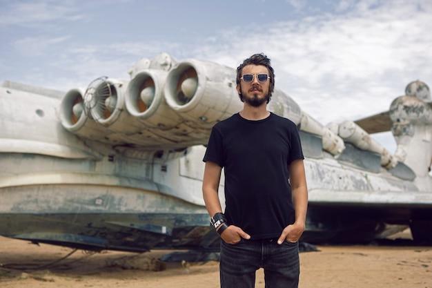 黒い服を着たロッカーの男は、ビーチで放棄された飛行機の背景に立っています