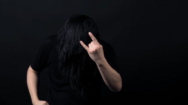 Рокер с длинными волосами и делает знак рок-н-ролла и качает головой в футболке черного цвета