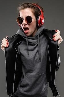 ロッカースタイルの女の子は黒い壁にヘッドフォンで音楽を楽しんでいます