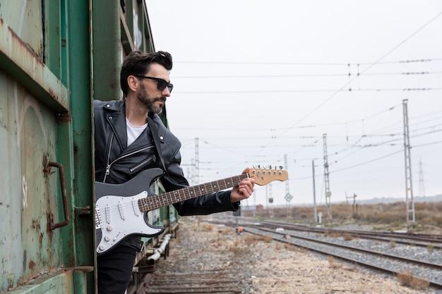 放棄された電車に乗ったサングラスとエレキギターのロッカー
