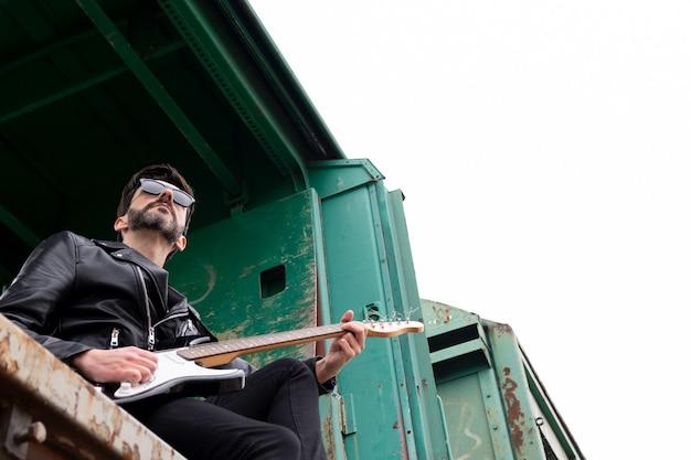 放棄された電車の車に座っているサングラスとエレキギターとロッカー