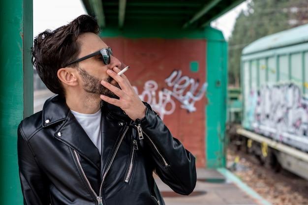 放棄された電車の車でタバコを吸うサングラスとエレキギターのロッカー