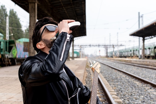 Rocker with sunglasses and electric guitar drinking whiskey from his flask on an abandoned train station.