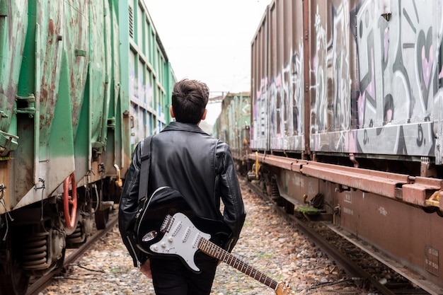 A rocker with sunglasses and his guitar walking among abandoned train cars.