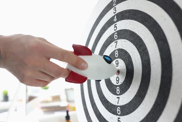Rocket in hands of businessman hitting darts target closeup