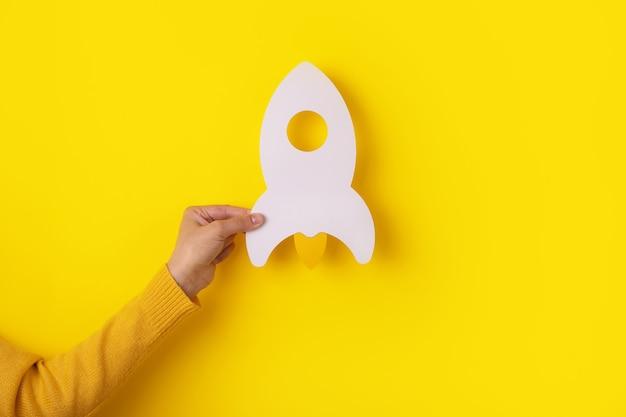 노란색 배경, 시작 사업 아이디어 위에 손에 로켓