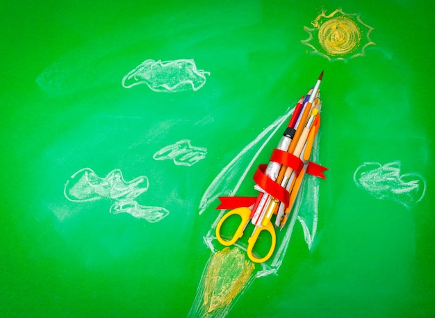 Rocket made from school supplies on green chalkboard