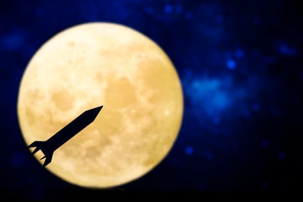 보름달을 통해 로켓 실루엣