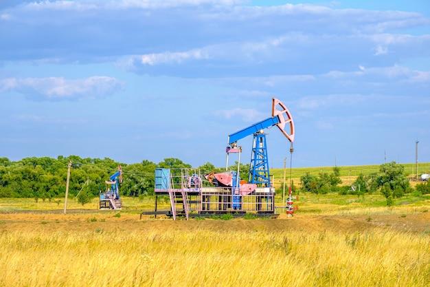 Кресло-качалка для добычи нефти в засушливой степи в солнечный день на фоне голубого неба.