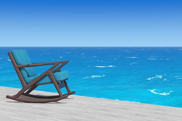 Кресло-качалка обитое синей тканью на деревянном полу перед крупным планом крайнего океана. 3d рендеринг