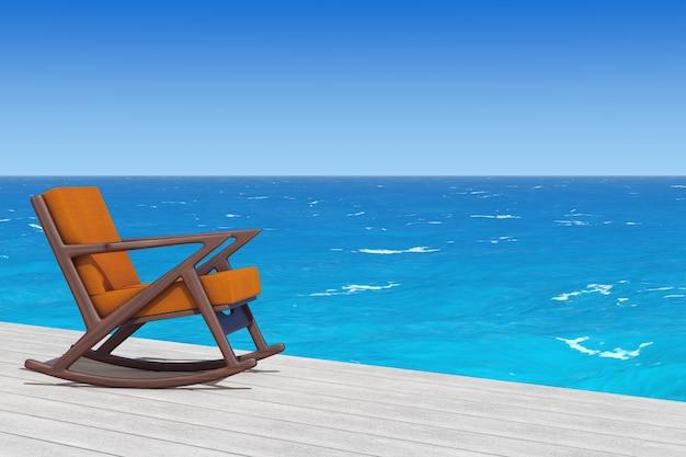 Кресло-качалка обитое оранжевой тканью на деревянном полу перед крупным планом крайнего океана. 3d рендеринг