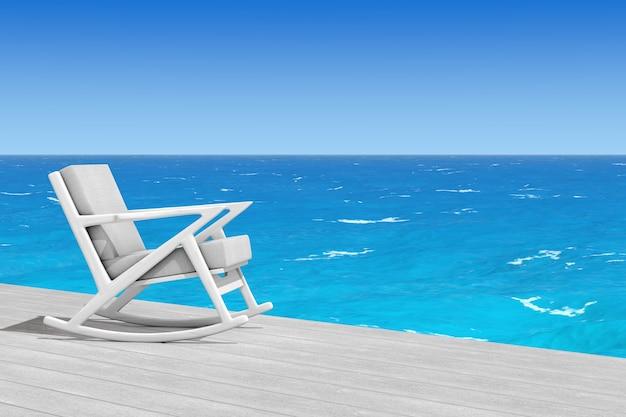 Кресло-качалка обитое белой тканью на деревянном полу перед крупным планом океана крайним. 3d рендеринг