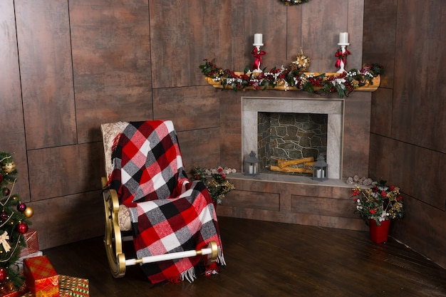 装飾されたモダンな炎の暖炉とクリスマスツリーのあるリビングルームの毛布付きロッキングチェア