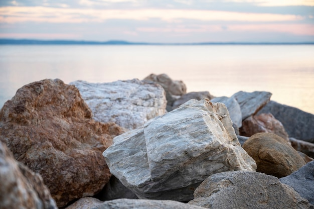 Rocks on the aegean sea coast at sunset, land in the distance in skala fourkas, greece