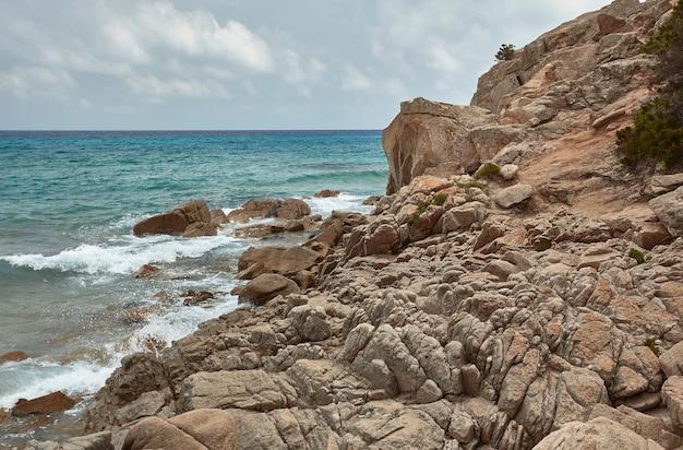 Скалы и утесы, образующие уникальный профиль в скалистой стене этой горы с видом на море.