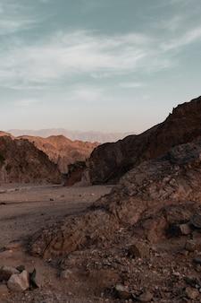 曇り空の下の砂漠の岩と丘