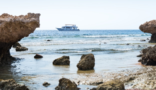 빈 해변의 바위와 돌, 배경의 바다에서 요트
