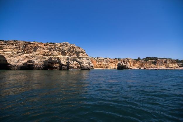 Rocce, scogliere e paesaggio dell'oceano al litorale in algarve, portogallo vista dalla barca