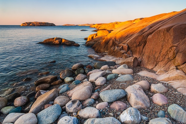 Rocks and cliffs on the shore of the sea during sunset in sweden