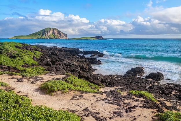 Скалы рядом с пляжем макапуу на фоне островов манана и каохикаипу, оаху, гавайи