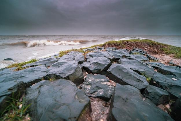 コケに覆われ、夕方の曇り空の下で波状の海に囲まれた岩