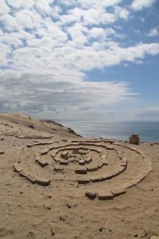 曇り空の下の砂浜で輪を形成する岩
