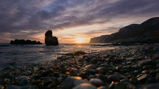 해변에서 일출 빛에 의해 조명하는 바위. 지중해