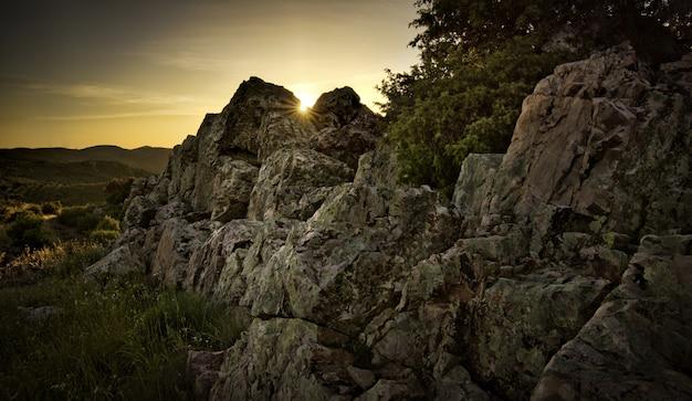 日没時の山の風景と太陽光線の岩